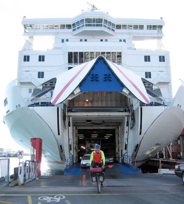 Cyclist escaping the open jaws of a ferry ship, Lofotan Island, Norway © 2012 Frosty Wooldridge