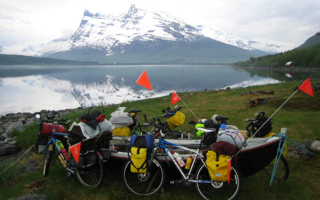 Touring bicycles stacked against a fishing dory on a fjord in Norway © 2012 Frosty Wooldridge